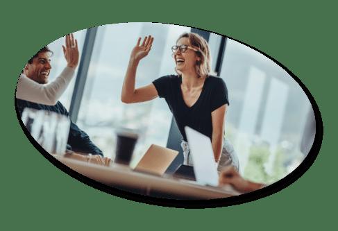 women high fives coworker in meeting