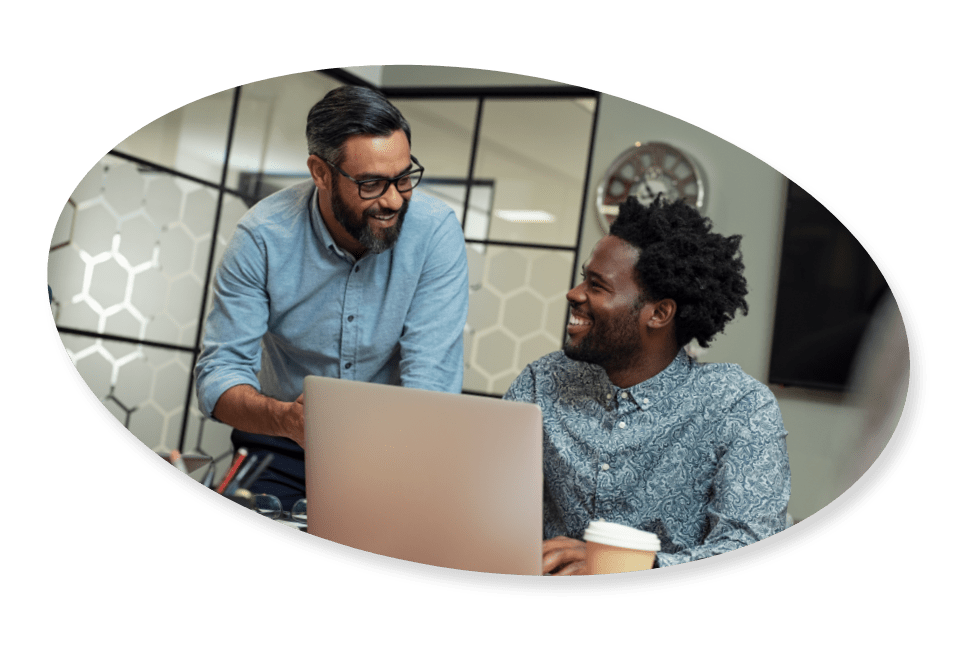 two happy coworkers in a meeting looking at a computer